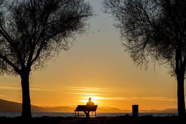 Person on a bench in front of a sunset